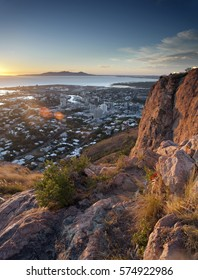 Overview of Townsville, Queensland, Australia from a lookout on a mountain peak over the rooftops of the city to the ocean beyond at sunset
