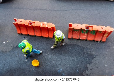 Overview of two construction workers with reflective vest and helmets on a street in New York City, USA