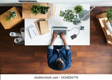 Overview of young businessman in denim jacket sitting by desk during work over business project in front of laptop