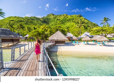 Overwater bungalow hotel resort in Tahiti, Moorea island. Person on holiday relaxing at French polynesia luxury destination.