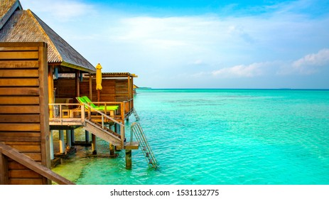 Overwater Bungalow looking over crystal clear turquoise water, luxury Maldives tropical island resort