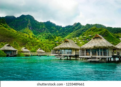 Overwater bungalows in the clear, vibrant turquoise waters of Moorea island and its famous lagoon, backed by tall mountains, in French Polynesia, in the south Pacific Ocean