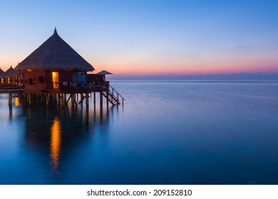 Overwater bungalows on the tropical island resort of Maldives at night.  Scenic sunset over the Ocean.