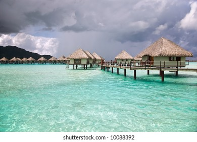 Over-water bungalows with storm on the background.