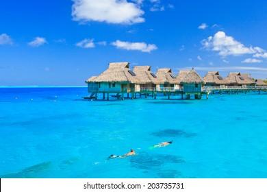 Overwater villas in blue tropical lagoon, Bora Bora, French Polynesia, South Pacific