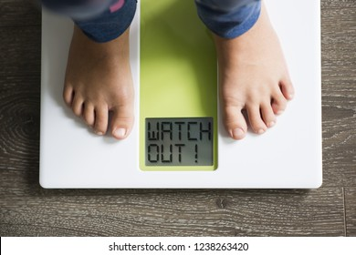 "Overweight alert for small child with ""watch out"" message on weight scale display"