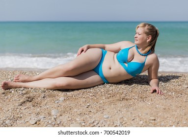 Overweight blond at the sea. Adult plump woman in blue bikini lying on pebble against the sea