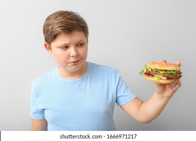 Overweight boy with burger on light background