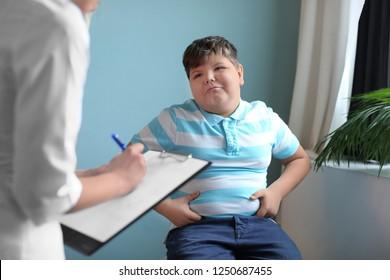 Menino com excesso de peso consultando com médico no escritório