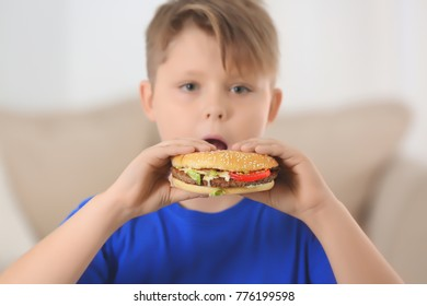 Overweight boy eating burger at home