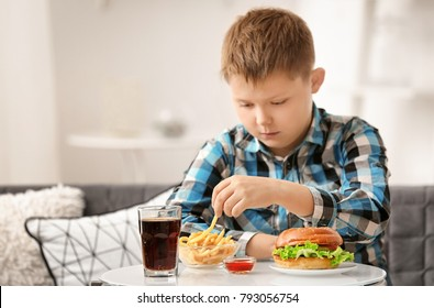 Overweight boy eating junk food at home