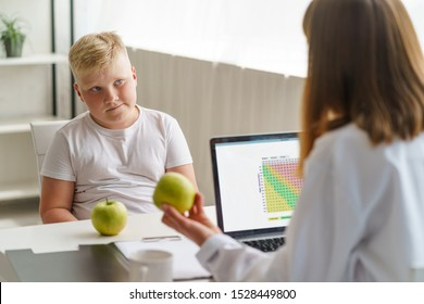 Overweight boy at a nutritionist appointment. Kid reluctant about his diet. Doctor holding an apple and talking about healthy food.