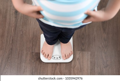 Overweight boy standing on floor scales indoors