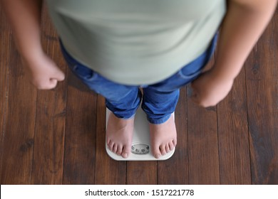 Overweight boy standing on floor scales indoors, above view