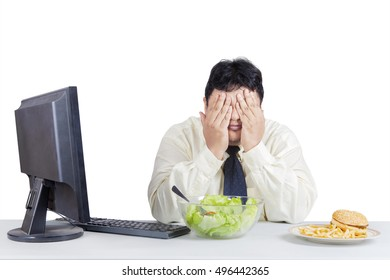 Overweight businessman try to diet while avoid temptation of foods with computer on the desk, isolated on the white background
