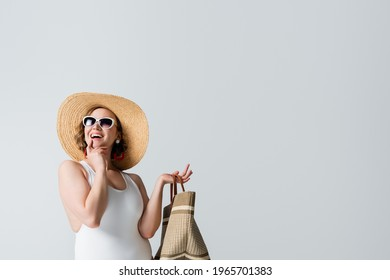 overweight and cheerful woman in straw hat, sunglasses and swimsuit holding bag isolated on white
