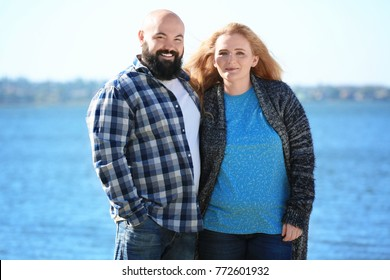 Overweight couple near river on sunny day