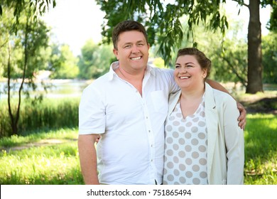 Overweight couple in park on sunny day