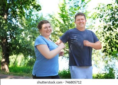 緑の公園で走る太り過ぎの夫婦
