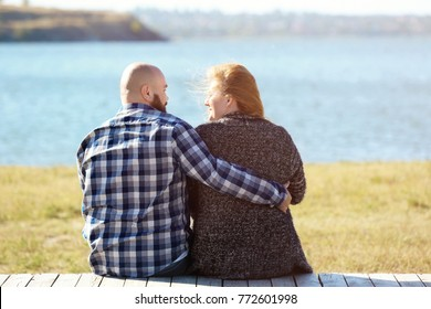 Overweight couple sitting on bench near river on sunny day
