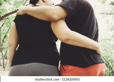 Overweight couple walking together hugging in park. Weight losing, outdoor activities, healthy lifestyle concept.