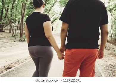 Overweight couple walking together in park. Weight losing, outdoor activities, healthy lifestyle concept.