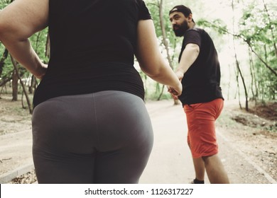 Overweight couple working out together. Husband supporting his wife in weight losing. Outdoor activities, fitness, sport, healthy lifestyle concept