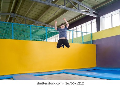Overweight cute little boy jumping on trampoline indoors in a sport center for kids