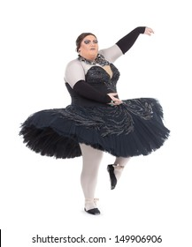 Overweight drag queen dancing in a tutu nimbly balancing on tiptoe with his foot raised in a fun caricature of a female ballet dancer, on white