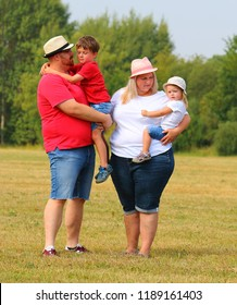 Overweight family together outdoor.  Parents with her kids enjoying life during summer vacations.