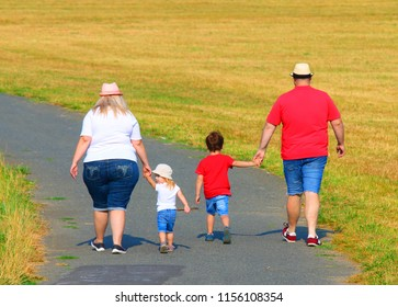 Overweight family walking on footpath. Hiking is outdoor sport for all. Summer vacations on countryside.