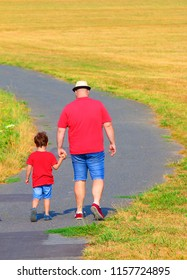 Overweight father with son walking on footpath. Hiking is outdoor sport for all. Summer vacations on countryside.