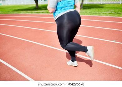 Overweight female in activeweat having run on stadium