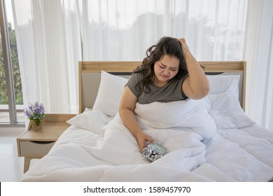 Overweight female (plus size Asian model) Big women , Fat people. lady lies in bedroom. Sleepy. Sleep difficult. Snooze the alarm. Don't want to get out of bed concept. Monday morning habit.