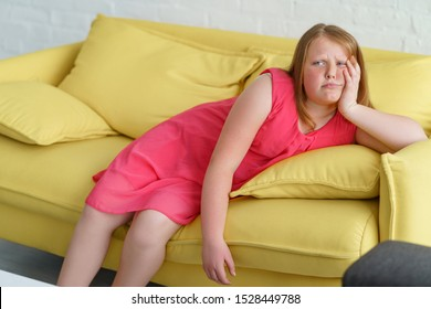 Overweight girl laying on a couch, lazy or tired of waiting. Dressed in light pink dress, she's giving a bored look.