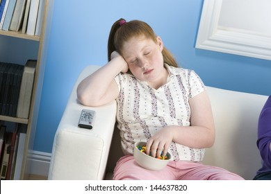 Overweight girl sleeping on sofa with bowl of sweets