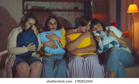 Overweight girls relaxing on couch surprised and scared watching horror movie. Beautiful plus size girlfriends at home party frightened watching thriller film on couch in living room