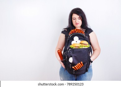 Overweight is a heavy luggage. Obese fat young woman with a great backpack full of junk food on her belly as a symbol of excess weight. Dieting, weight losing, motivation concept