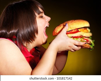Overweight hungry woman eating hamburger.