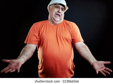 Overweight industrial supervisor gesturing disappointed. All over black background.