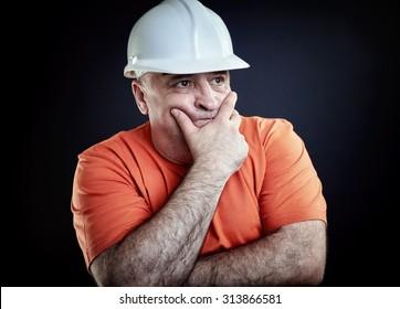 Overweight industrial supervisor wearing helmet and hands folded on chest. Portrait over black background, studio shoot.