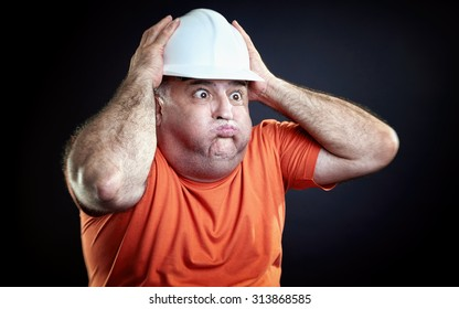 Overweight industrial worker gesturing hopeless. Hands over helmet, all over black background.