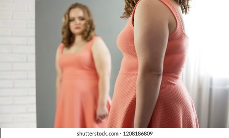 Overweight lady crying in front of mirror upset about appearance, insecurities