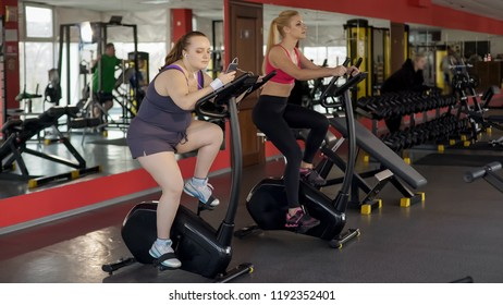 Overweight lady riding sluggishly exercise bike and scrolling smartphone, lazy