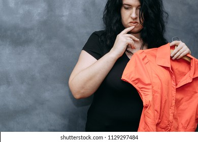 Overweight, low self-esteem, body shaming. Obese shy woman hesitating to wear vibrant colored shirt