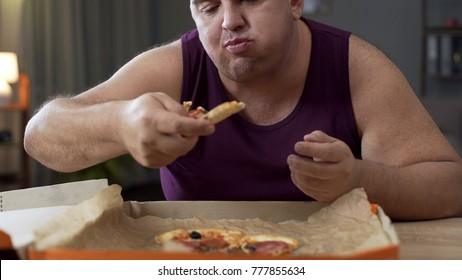 Overweight male eating pizza with delight at night, addiction to unhealthy food