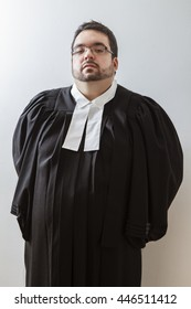 Overweight man, with arms behind his back, in canadian lawyer toga against a white background