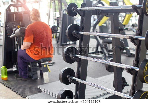 An overweight man exhausted with exercising in fitness center.