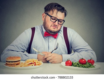 Overweight man in formal outfit looking at saladâ? with hate while craving juice hamburger.