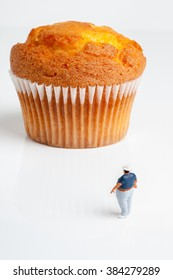 Overweight man looking up at an enormously large muffin a portion size or obesity concept